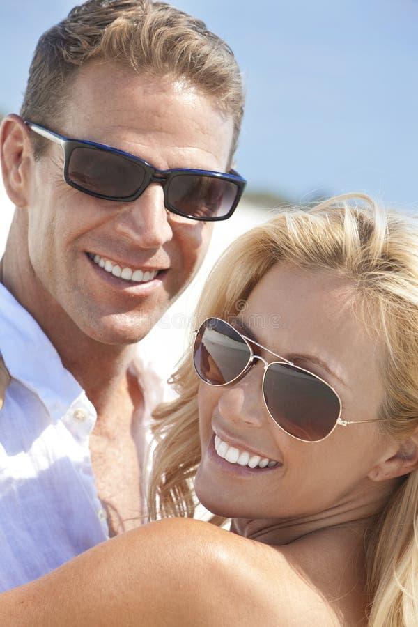 Couples heureux d'homme de femme dans des lunettes de soleil à la plage image stock