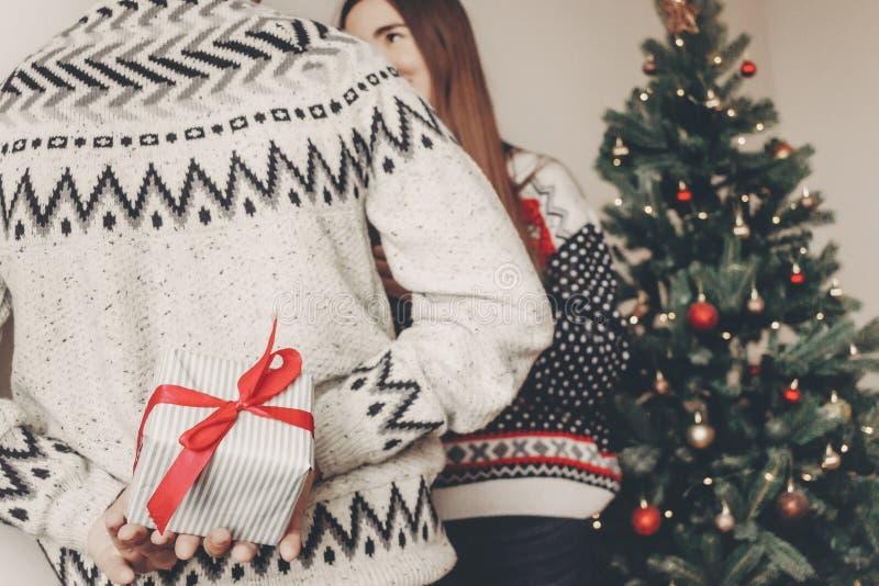 Couples heureux dans des chandails élégants échangeant des cadeaux dans le roo de fête image stock