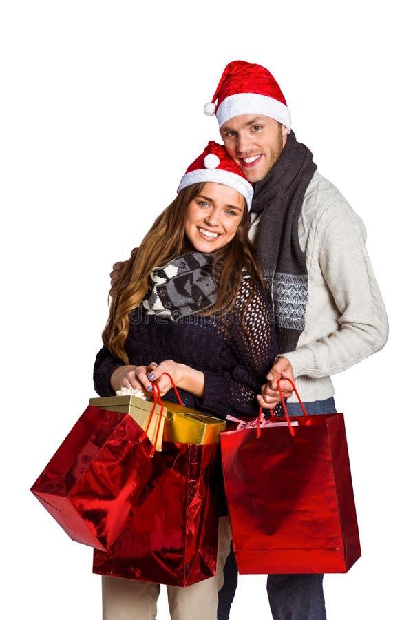 Couples heureux dans des chapeaux de Santa avec des cadeaux photographie stock libre de droits
