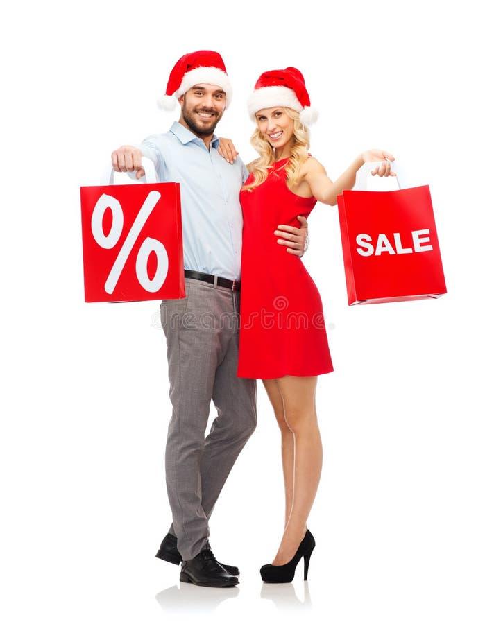 Couples heureux dans des chapeaux de Santa avec les paniers rouges images stock