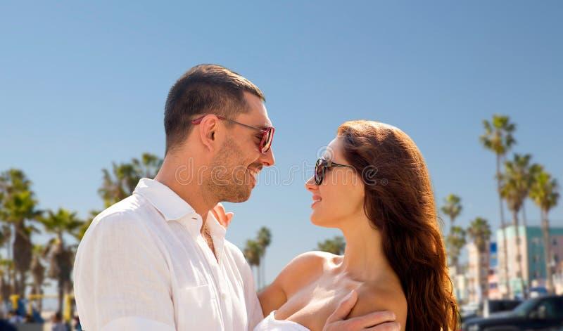 Couples heureux dans des lunettes de soleil au-dessus de plage de Venise photo libre de droits