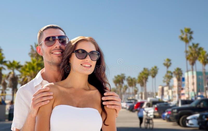 Couples heureux dans des lunettes de soleil au-dessus de plage de Venise image libre de droits