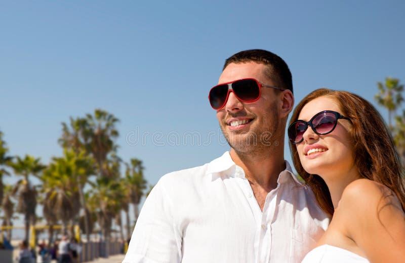 Couples heureux dans des lunettes de soleil au-dessus de plage de Venise image stock