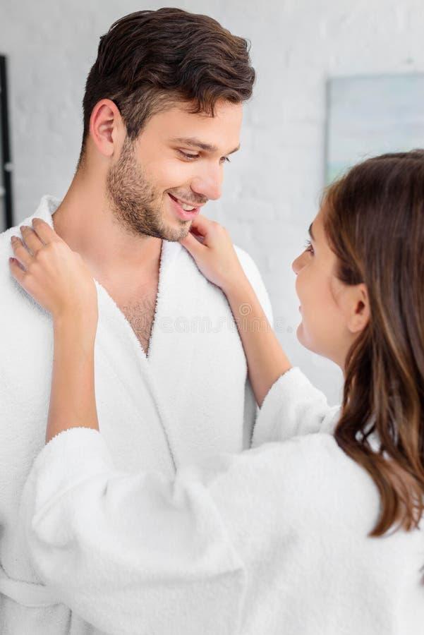 couples heureux dans des peignoirs blancs se tenant ensemble image libre de droits