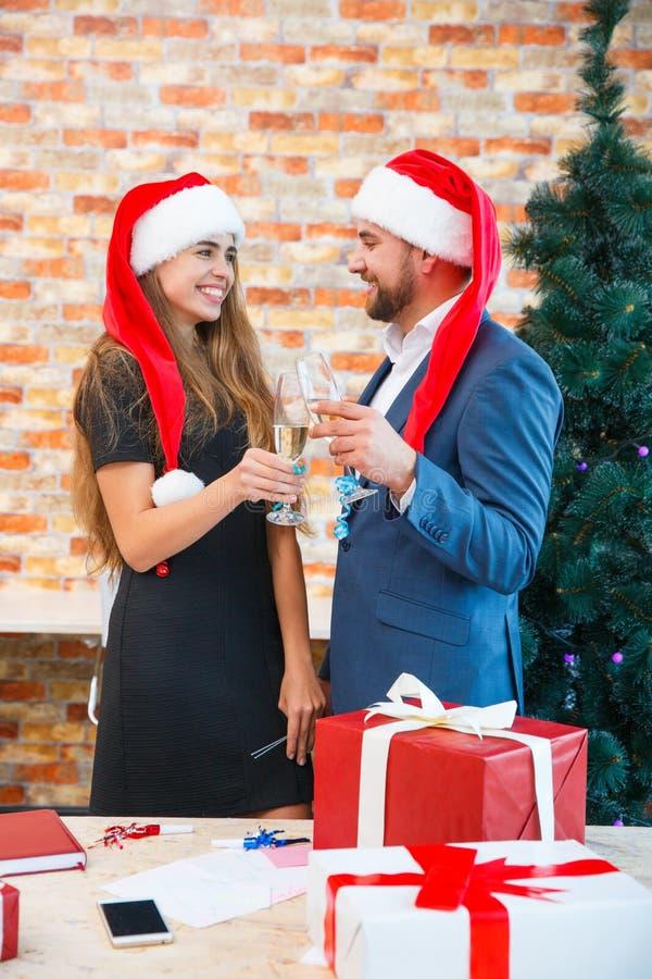 Couples heureux dans l'amour dans des chapeaux de Noël ayant l'amusement sur un fond brouillé Concept domestique de nouvelle anné image stock