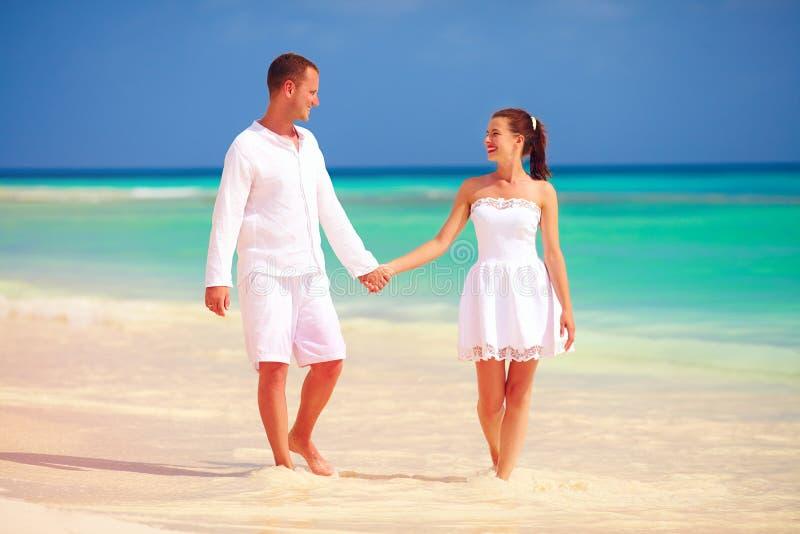 Couples heureux dans l'amour marchant sur la plage tropicale photographie stock libre de droits