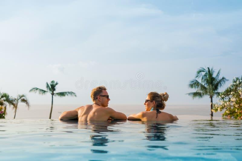 Couples heureux dans la piscine d'infini image stock