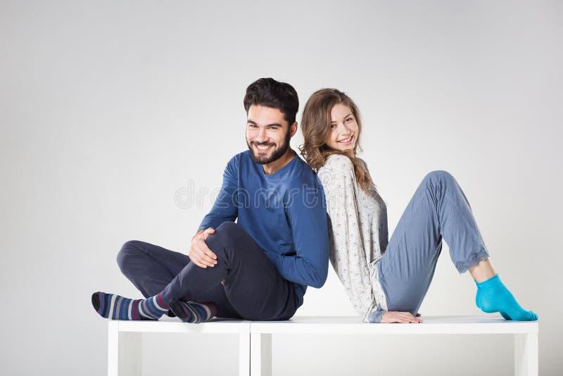 Couples heureux dans le pyjama posant dans le studio image stock