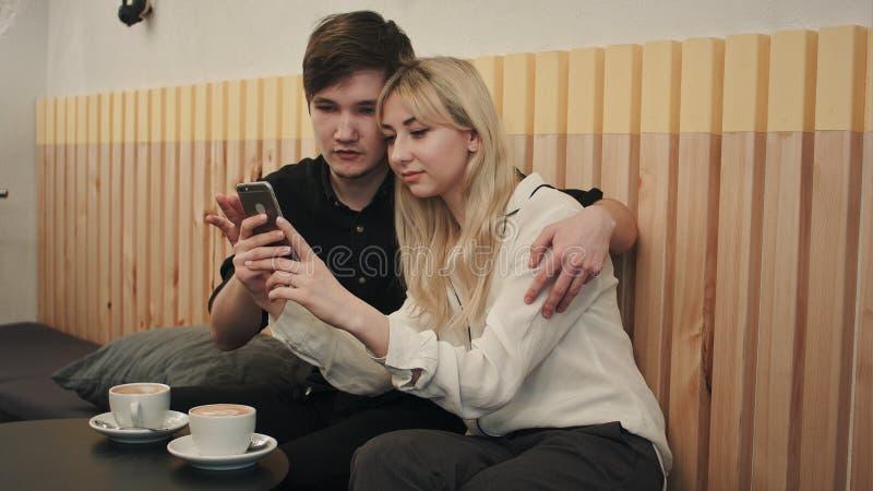Couples heureux dans un café prenant le petit déjeuner et et à l'aide du téléphone portable images stock