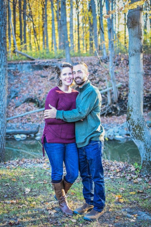 Couples heureux dans une forêt en automne photographie stock libre de droits