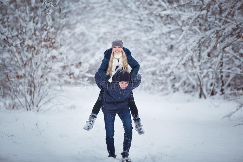 Couples heureux de course de l'hiver Homme donnant le tour de ferroutage de femme des vacances d'hiver dans la forêt neigeuse photo stock