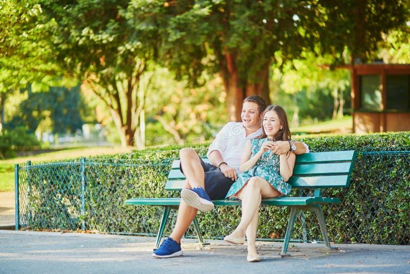 Couples heureux de datation sur un banc en parc parisien image libre de droits