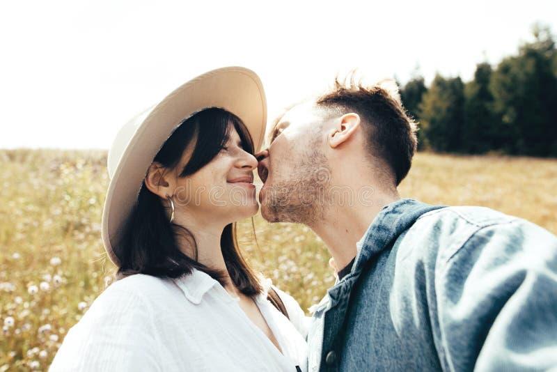 Couples heureux de hippie faisant le selfie et l'embrassant en montagnes ensoleillées Jeune famille élégante prenant la photo dan photo libre de droits