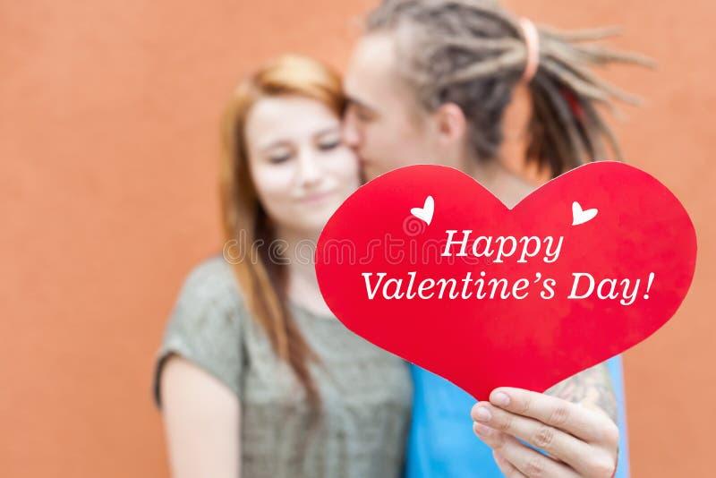Couples heureux de jour de valentines tenant le symbole rouge de coeur photo stock