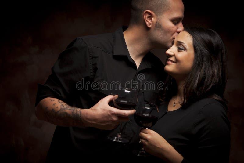 Couples heureux de métis flirtant et tenant des verres de vin images libres de droits