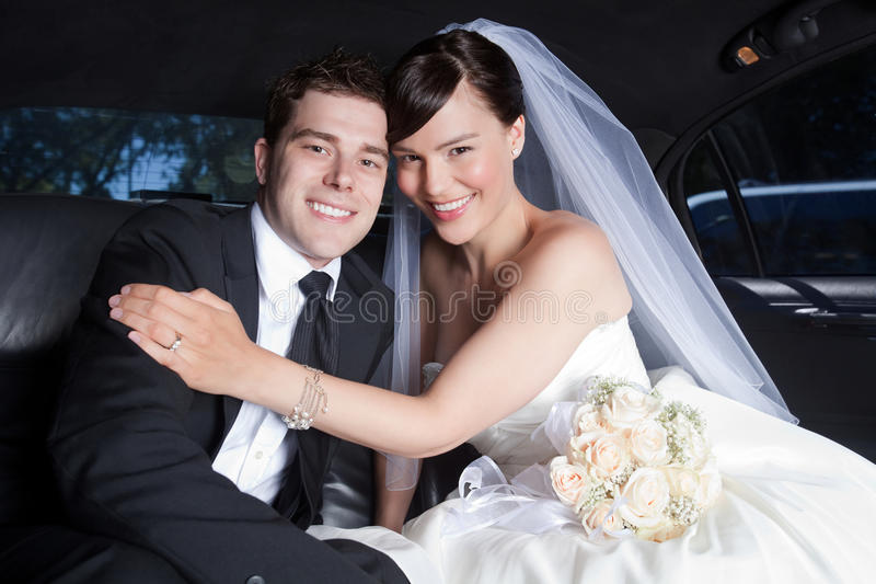 Couples heureux de mariage dans la limousine photographie stock libre de droits