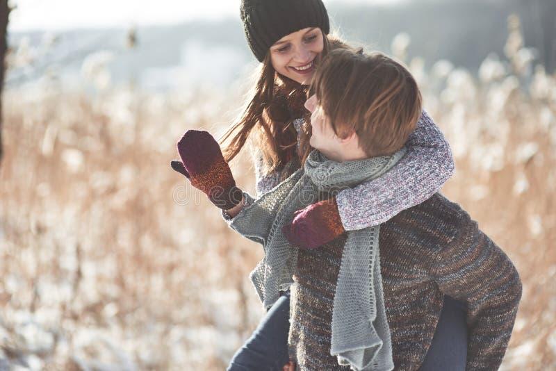 Couples heureux de Noël dans l'étreinte d'amour dans la forêt froide d'hiver neigeux, l'espace de copie, célébration de partie de photo stock