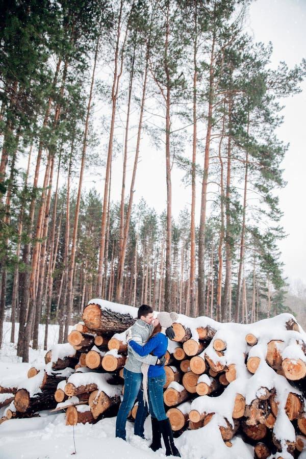 Couples heureux de Noël dans l'étreinte d'amour dans la forêt froide d'hiver neigeux, l'espace de copie, célébration de partie de images stock