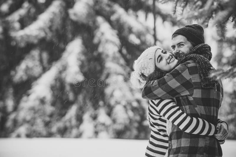 Couples heureux de Noël dans l'amour dans la forêt froide d'hiver neigeux photos libres de droits