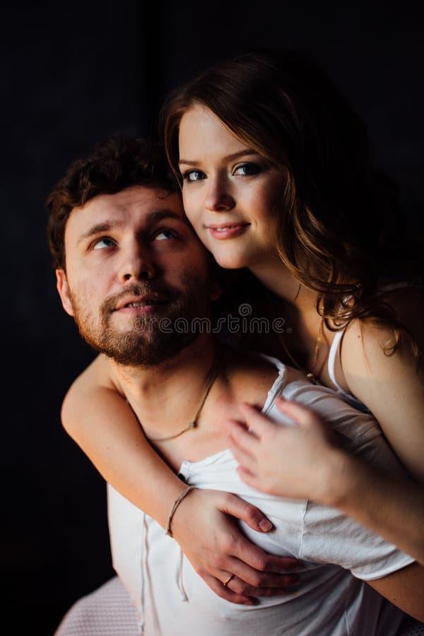 Couples heureux des amants chez l'homme de embrassement de fille de pyjamas par derrière image stock