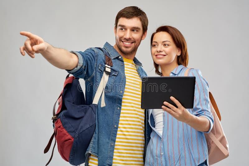 Couples heureux des touristes avec la tablette photo stock