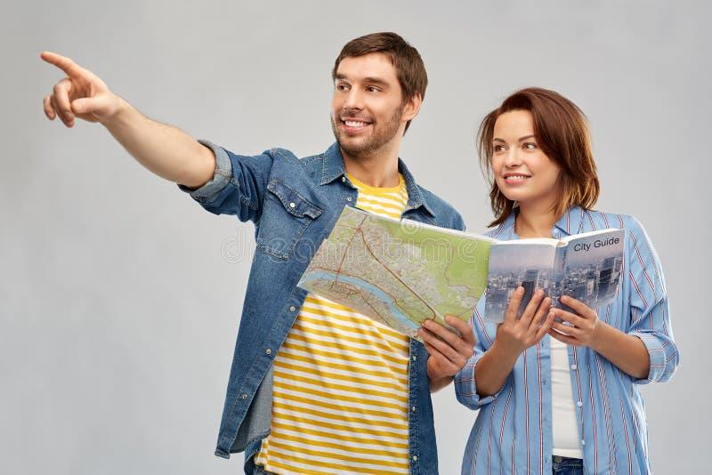 Couples heureux des touristes avec le guide et la carte de ville images stock