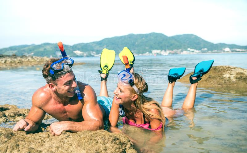 Couples heureux des vacances dans l'amour ayant l'amusement à l'eau sur la plage tropicale en Thaïlande avec le masque de prise d photos libres de droits