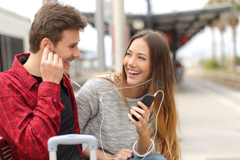 Couples heureux des voyageurs partageant la musique en vacances images stock
