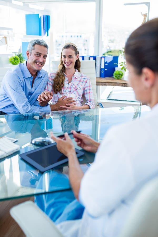 Download Couples Heureux Discutant Avec Le Docteur Photo stock - Image du indoors, patient: 56482478