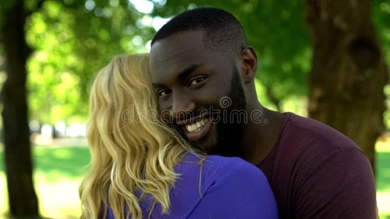 Couples heureux emball?s m?lang?s, femme de embrassement d'homme de couleur, relations interraciales photo stock