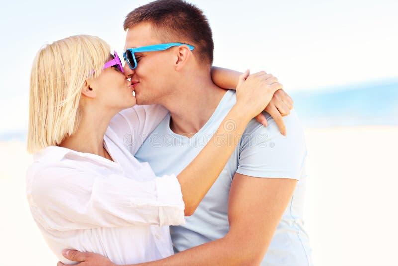 Couples heureux embrassant à la plage images stock