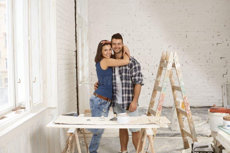 Couples heureux embrassant dans en construction à la maison photo libre de droits