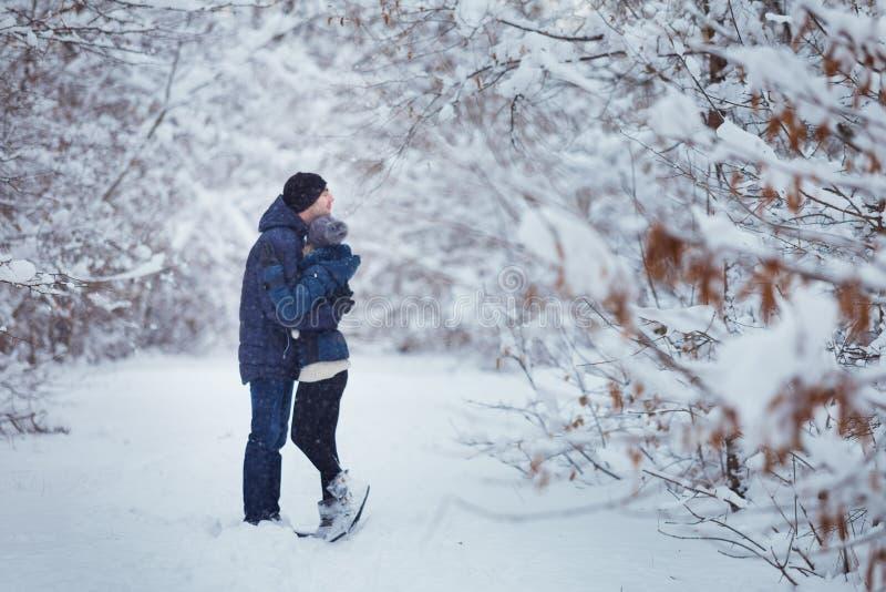 Couples heureux embrassant dehors en parc de neige Vacances de l'hiver Image brouillée photographie stock