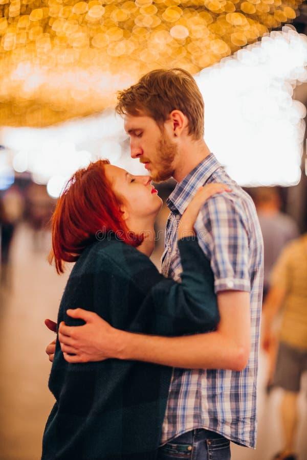 Couples heureux embrassant et embrassant le soir sur les guirlandes légères images stock