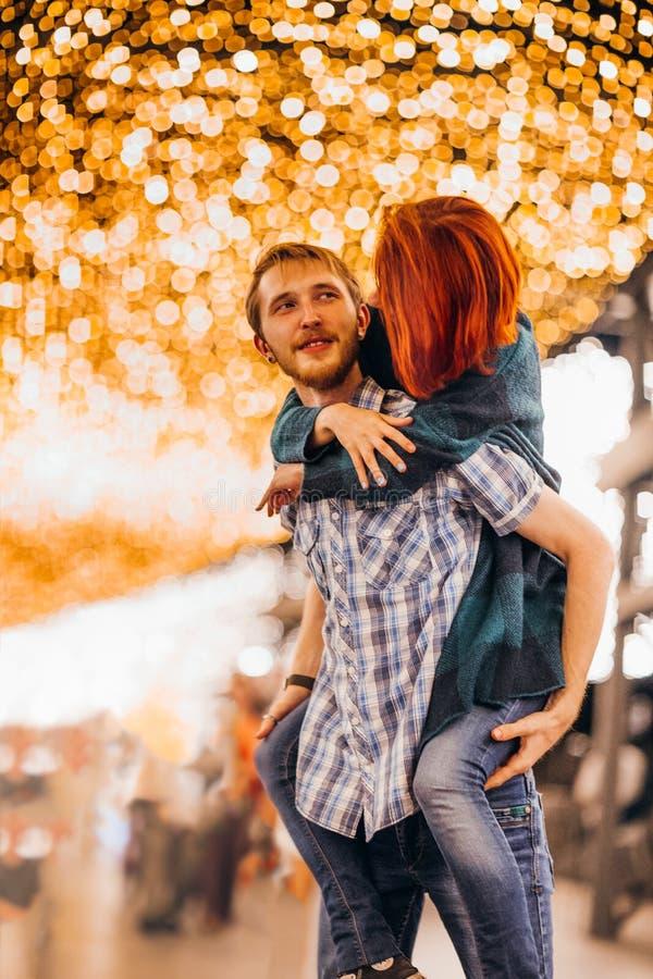 Couples heureux embrassant le soir sur les guirlandes légères images libres de droits