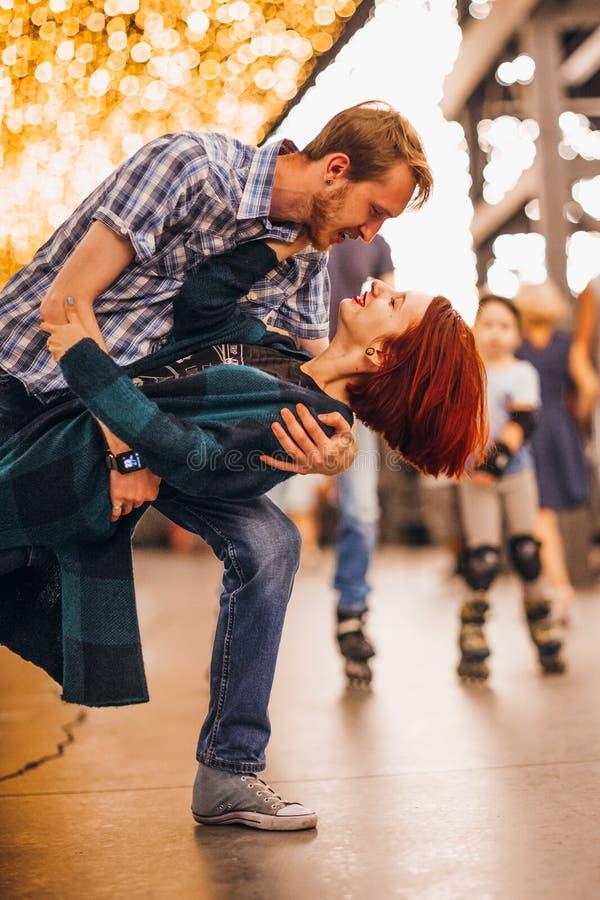 Couples heureux embrassant le soir sur les guirlandes légères images stock