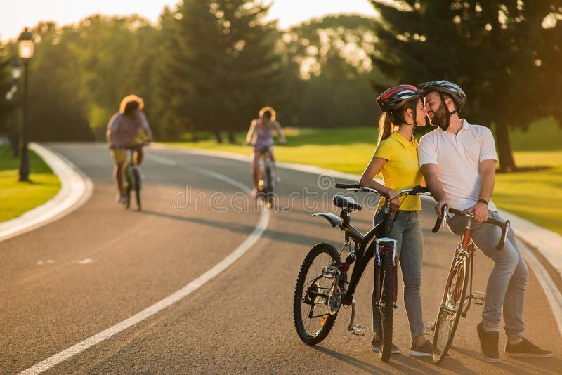 Couples heureux embrassant pendant un tour de bicyclette dehors images libres de droits