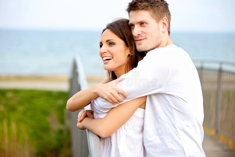 Couples heureux embrassant tandis qu'en stationnement image stock