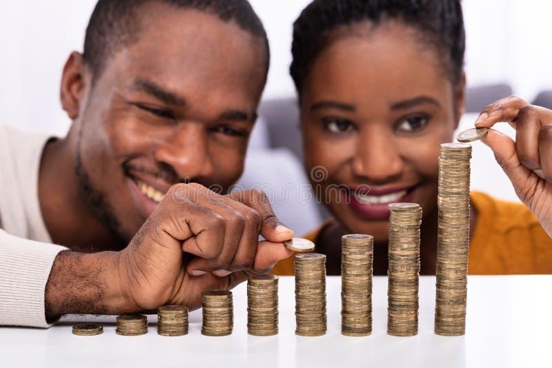 Couples heureux empilant des pi?ces de monnaie images stock