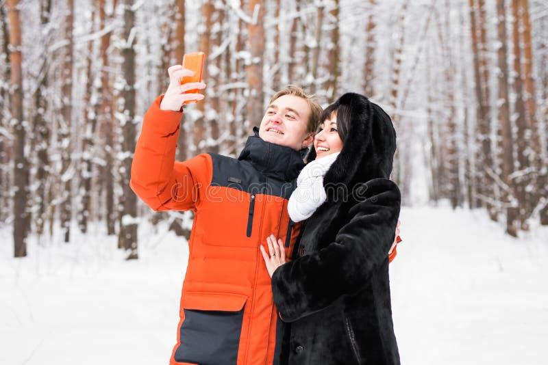 Couples heureux en hiver prenant des photos de lui-même avec le smartphone image stock