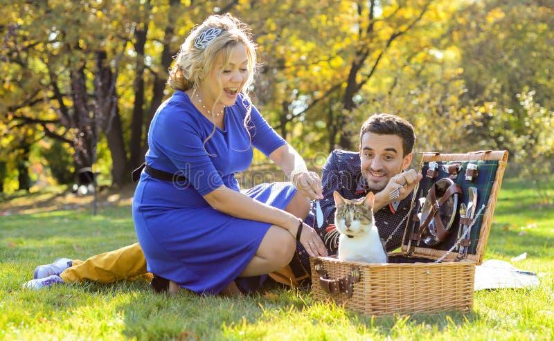 Couples heureux et souriants enceintes sur le pique-nique avec le chat photos libres de droits