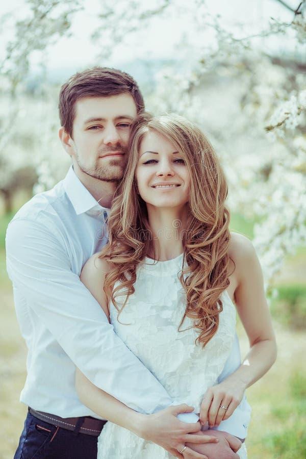 Couples heureux extérieurs dans l'amour posant en parc de floraison Jeune garçon et fille ayant l'amusement extérieur photo libre de droits