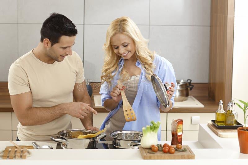Couples heureux faisant cuire dans la cuisine images libres de droits