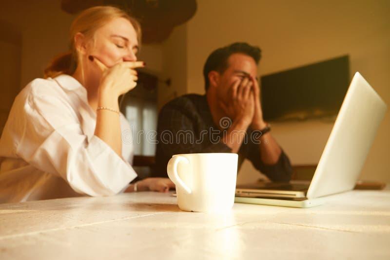 Couples heureux faisant des affaires fonctionnant ensemble au petit bureau sur l'ordinateur portable image libre de droits
