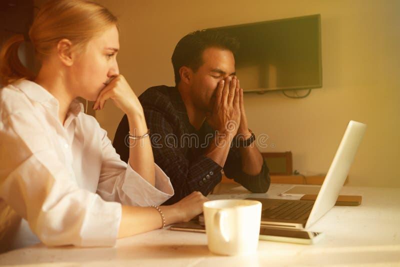 Couples heureux faisant des affaires fonctionnant ensemble au petit bureau sur l'ordinateur portable photographie stock libre de droits