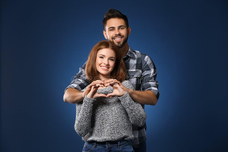 Couples heureux faisant le coeur avec leurs mains sur le fond de couleur Célébration de Saint-Valentin de saint photographie stock libre de droits