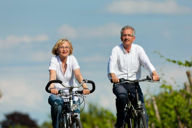 Couples heureux faisant un cycle à l'extérieur en été image libre de droits