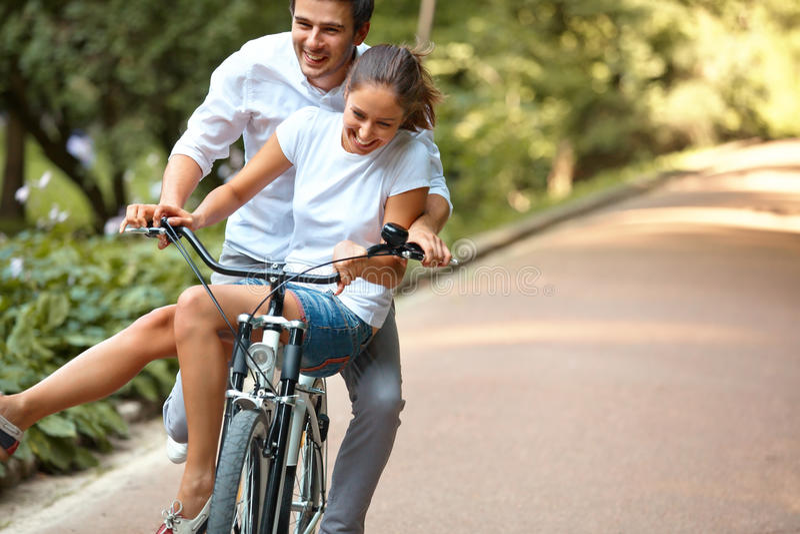 Couples heureux faisant un cycle en parc d'été image libre de droits