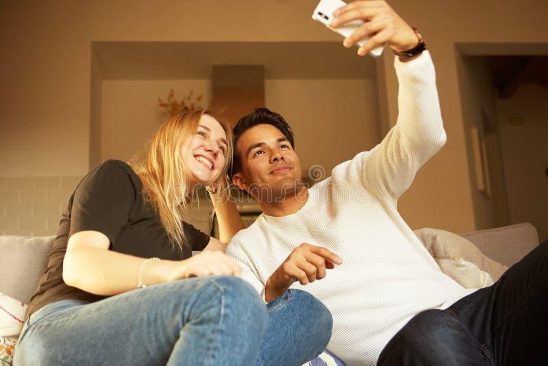 Couples heureux gais aimants prenant le selfie sur le sofa à la maison images stock