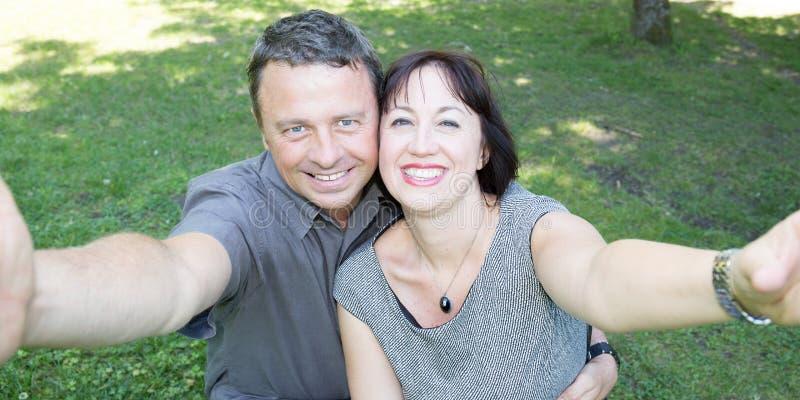 Couples heureux gais prenant le selfie dans le jardin image stock